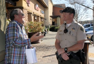 Wildrose Ranch resident John Watson talks to the deputy in charge of school safety about traffic issues when parents drop off and pick up students at Temescal Valley Elementary School.