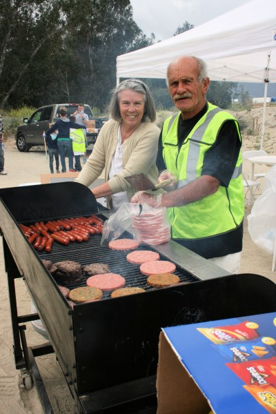 Helen and Don McGlaughlin grill the hamburgers and hot dogs.