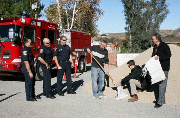 GOT SANDBAGS: Pictured are Public Safety Chairman Rob Mucha shoveling gravel into a bag held by Eric Werner, president of Werner Corp., as Robert Lizano, general manager of Tom's Farms looks on. Station 64 firefighters, pictured from left, are firefighter/paramedic Brandon Forsberg, Engineer Kevin Hansen and Capt. Lorne Ellickson. Thank you to all for providing this community service.